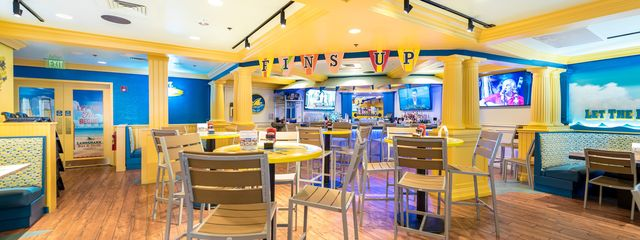 Bright blue and yellow bar interior with chairs and tables