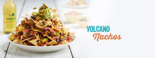 Nachos on a white plate with text Volcano Nachos
