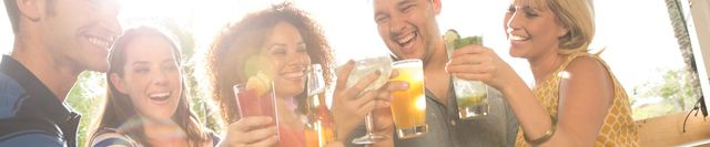 Group of friends laughing and doing cheers with various drinks